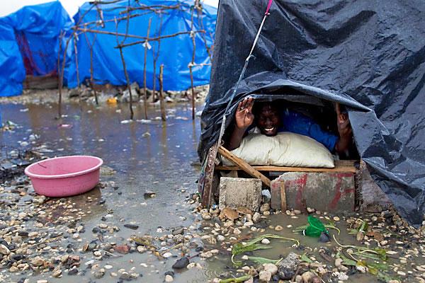 Haiti-rain-man-peering-from-tarp-tent-031910-by-Ramon-Espinosa-AP, Opportunities are washing away in Haiti, World News & Views