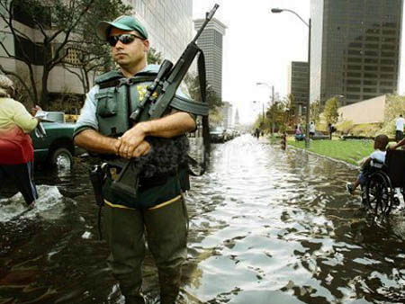 New-Orleans-Katrina-cop-in-flooded-street-by-AFP, After Katrina, New Orleans cops were told they could shoot looters, National News & Views