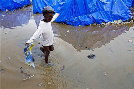 Haiti-camp-child-wading-after-rain-0310-by-Ramon-Espinosa-AP, Nine months after the quake, a million Haitians slowly dying, World News & Views