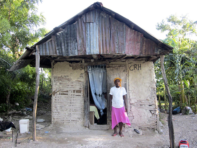 Haitian-woman-returns-to-family-home-Jacmel-after-tent-burned-1010-by-Macatney-Lubin-Plan-International1, Million plus remain homeless and displaced in Haiti one year after quake, World News & Views