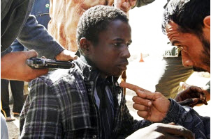 Anti-Qaddafi-forces-threaten-young-African-0311-by-Goran-Tomasevic-Reuters, Libya, getting it right: a revolutionary pan-African perspective, World News & Views