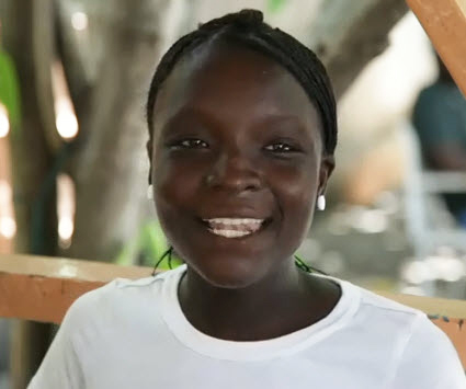 """A little girl speaks up: """"Since Aristide left, we can't find food, we can't go to school. Obama, send Aristide back to this country to give us the strength to build schools, to find work and to feed out families,"""" she declares. – Video frame: Paul Burke"""