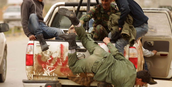 Libyan-rebel-falls-off-truck-fleeing-back-to-Benghazi-031511-by-Patrick-Baz-AFP, U.S., NATO and the attacks against Libya, World News & Views