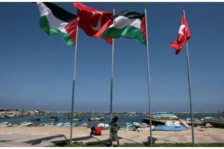 Palestinian-boy-looks-at-the-Turkish-and-Palestinian-flags-at-monument-to-nine-Turks-murdered-on-first-flotilla-0611-by-Mahmud-Hams-AFP, Alice Walker: Why I'm joining the Freedom Flotilla to Gaza, World News & Views