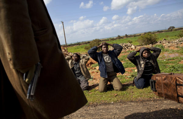 Anti-Qaddafi-militia-stop-3-Black-Africans-at-checkpoint-Libya-0311-by-Kevin-Frayer-AP, Ethnic cleansing of Black Libyans, World News & Views