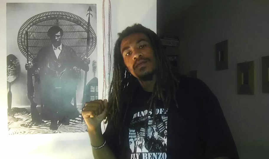 Fly-Benzo-DeBray-Carpenter-with-classic-Huey-Newton-poster, Police critic Fly Benzo keeps catching hell since police murder of Kenneth Harding, Local News & Views