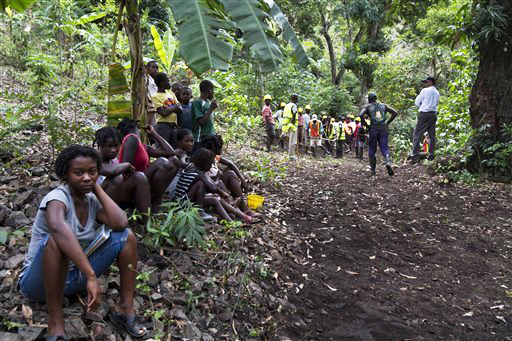 Haitians_watch_workers_build_road_to_mining_exploratory_sites_in_Northern_mountains_041012_by_Dieu_Nalio_Chery_AP, Signs of the times in Haiti: The military, money and meaning of an occupation, World News & Views