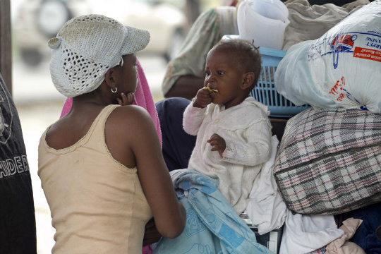 Mother_child_sheltering_from_Hurricane_Isaac_082512_by_Reuters, The UN's cholera epidemic in Haiti, World News & Views