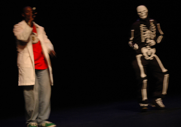 Naru-Kwina-of-Hip-Learning-on-stage-w-dancing-skeleton, Hip Learning: an interview wit' founder Naru Kwina, Culture Currents
