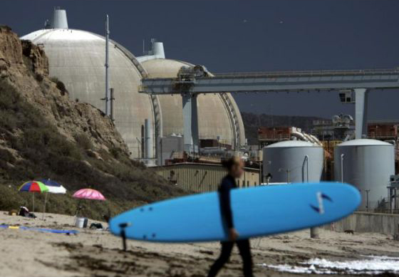 Surfer at San Onofre State Beach in shadow of San Onofre Nuclear Generating Station by Orange County Register