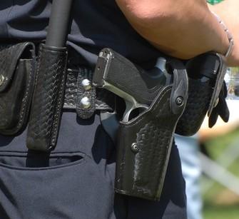 White cop closeup of gun, belt