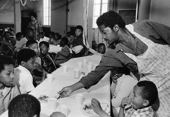Black Panthers- Charles Bursey serving breakfast by Pirkle Jones