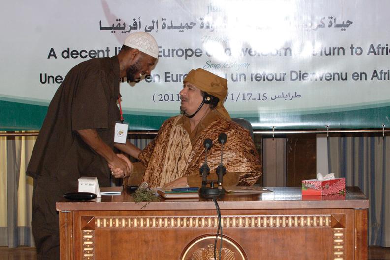 Malcolm, Muammar Qaddafi at African Migrants Conf 011711 by JR, web