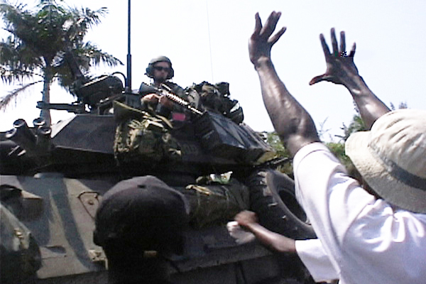 Haiti protester, fingers outstretched 5 years, defies US soldier in APC aiming assault rifle 030804 by Kevin Pina, Haiti Information Project