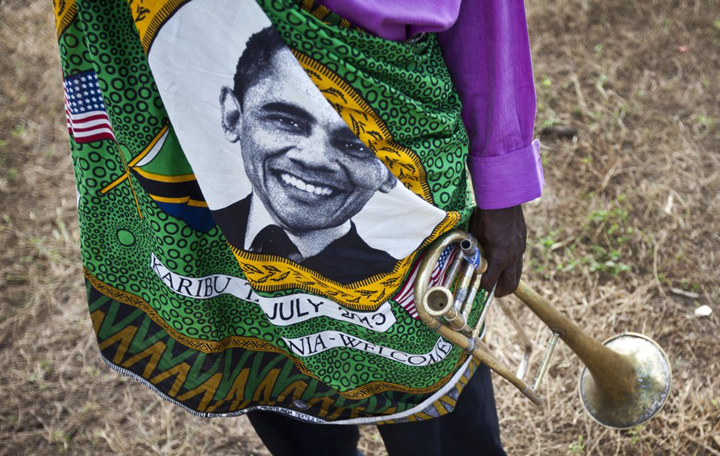 A member of the brass band waiting to welcome President Obama to the State House in Dar es Salaam for a meeting with Tanzanian President Jakaya Kitwete on July 1 wears clothing adorned with Obama's smiling face. Some Africans, like some African Americans, still cling to the hope that Obama is not only their brother but a friend. – Photo: Ben Curtis, AP