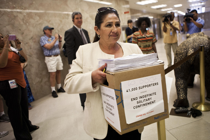 Dolores Canales carries papers and a box representing 60,000 signatures protesting indefinite solitary confinement in California prisons, to Governor Jerry Brown's office in Sacramento