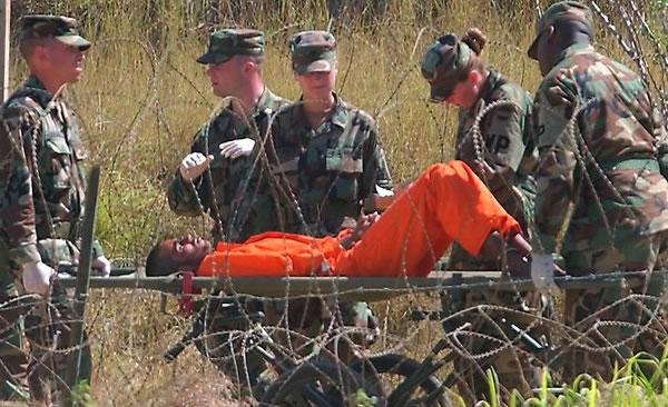 Guantanamo hunger striker on gurney, guards