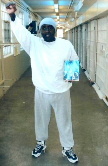 Kenny Zulu Whitmore standing, fist, holding Robert King's book 2008