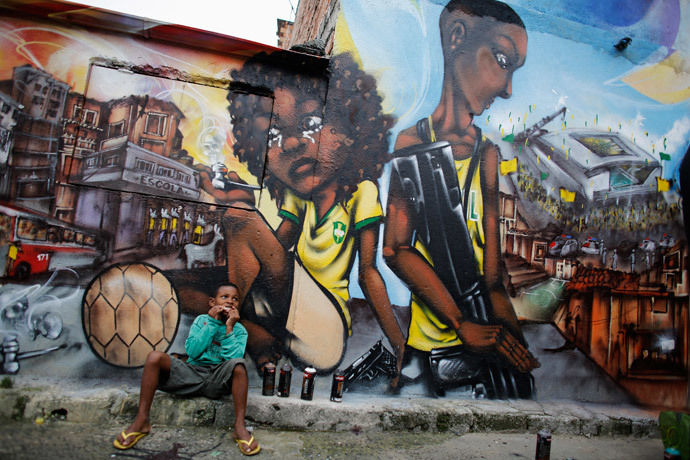 """Ryan, 9, sits in front of graffiti painted by members of Unidentified Graffiti Artists (OPNI) protesting the 2014 World Cup in the Vila Flavia """"slum"""" of Sao Paulo on May 28, 2014. – Photo: Nacho Doce, Reuters"""