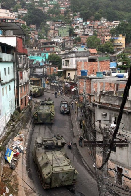 """Preparation for two sporting events, the 2014 World Cup and 2016 Olympics, is the excuse for forcing the eviction of Brazilians who live in the favelas that cling to the mountains above Rio de Janeiro and Sao Paolo. As many as 1.5 million families live within the """"urban renewal"""" construction zones. The Brazilian troops driving out their own people learned the techniques for brutally occupying poor neighborhoods in Haiti, where Brazil's """"peacekeepers"""" lead the U.N. mission, MINUSTAH. Here, the Brazilian Navy's armored vehicles patrol the streets during the occupation of the Rocinha favela on Nov. 13, 2011, in preparation for eviction and demolition. – Photo: Marcelo Sayao, EPA"""