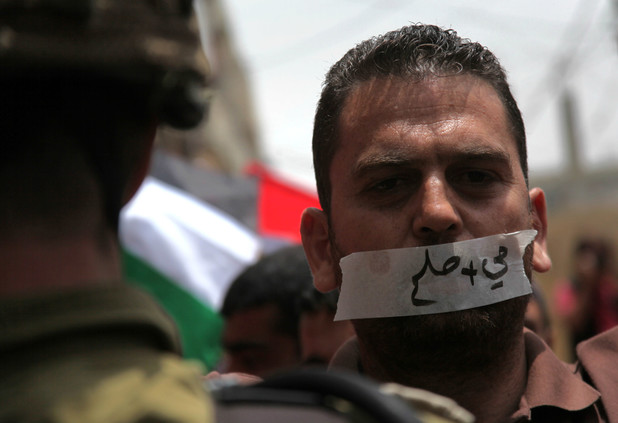 """A protester wears tape on his mouth reading """"water and salt"""" during a rally in solidarity with hunger striking prisoners at al-Aroub refugee camp near the occupied West Bank city of Hebron. – Photo: Mamoun Wazwaz, APA"""
