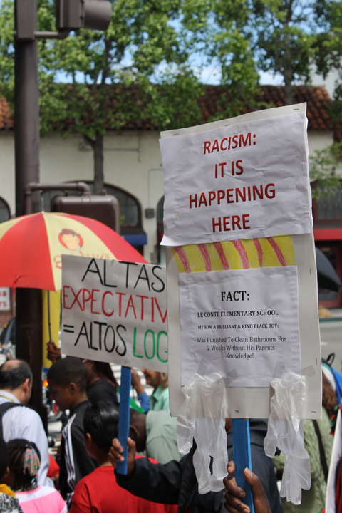 Rally signs, held by marchers in front of Berkeley Unified School District, draw attention to the educational racism in Berkeley. – Photo: Laura Savage