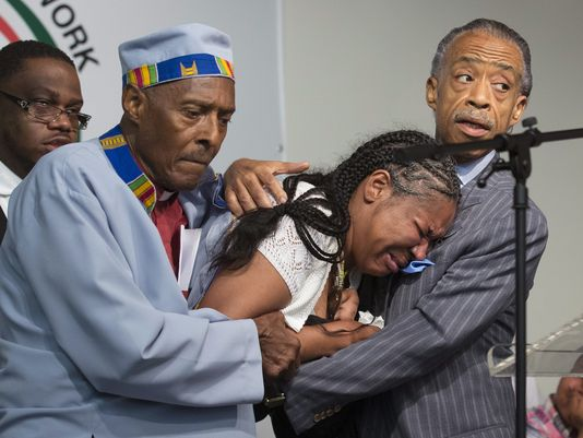 Eric Garner's wife Esaw collapses from grief, supported by Rev. Herbert Daughtry and Rev. Al Sharpton at the National Action Network rally on Saturday, July 19, the day after Eric was killed. – Photo: John Minchillo, AP