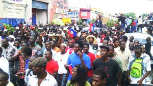 When former President Aristide was summoned to court on May 8, 2013, thousands of Haitians surrounded his car to protect him.