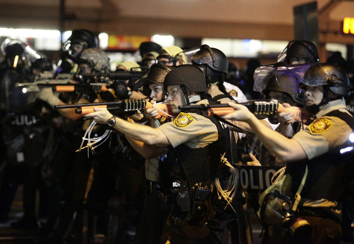Police point their guns at the rebels. The rage and repression unleashed by Michael Brown's murder has brought welcome attention to the militarization of police. – Photo: Joshua Lott, Reuters