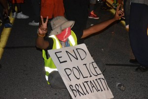 """It's not even a race war. It's about cops killing people and beating people."" says a masked Ferguson resident sitting in the middle of the street in protest of the police shooting of unarmed teenager Michael Brown and the violent police response to the protests that followed. – Photo: James Cooper"