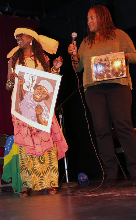 Djialli Phavia Kujichagulia holds a piece of iconic art created by Emory Douglas for The Black Panther newspaper that Emory gave to Dr. Ratcliff for his birthday. Beside her is Dr. Siri Brown, chair of the Merritt College African American Studies Department. – Photo: Malaika Kambon