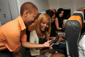 A flight attendant helps passengers check out in-flight wi-fi.
