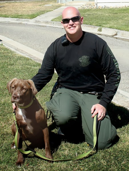 """This friendly looking pair began """"welcoming"""" visitors to Deuel Vocational Institution, a California state prison in Tracy, last October. Molly is DVI's first drug sniffing dog, and correctional officer Robert Willcox is her handler."""
