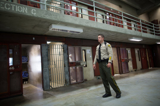 Officer Vickjord walks the floor of the 4B SHU at Corcoran State Prison. The prison started accepting inmates in 1988. – Photo: Grant Slater, KPCC