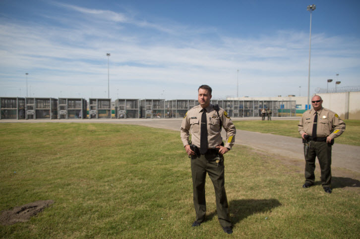 """Officers Vickjord and Mayo stand guard in the """"exercise yard"""" for prisoners in the SHU – one prisoner to each cage. – Photo: Grant Slater, KPCC"""