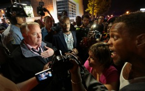 "In a story headlined, ""Ferguson Police Chief March Backfires,"" The Daily Beast reports: ""Hours after issuing an apology to the family of Michael Brown, Ferguson Police Chief Thomas Jackson attempted to march with protesters, many of whom are calling for his resignation. … 'I don't think he was marching with the protesters more than 30 seconds before the riot cops came out into the crowd and tried to get themselves closer to him and protect him, said Antonio French, a St. Louis elected official."" Brutal arrests ensued. – Photo: Robert Cohen, St. Louis Post-Dispatch"