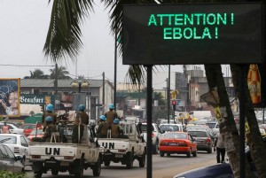 U.N. troops patrolling Abidjan, Ivory Coast, pass a sign warning of Ebola. Africa needs healers, not soldiers.