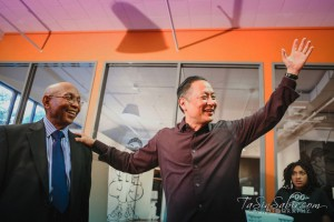 San Francisco's elected, best-in-the-nation public defender Jeff Adachi has kind words for his friend, Dr. Willie Ratcliff, at the BMAN reception in the spacious lobby of the African American Art and Culture Complex, as Joyous deAsis, youth writer with Poor News Network, looks on. – Photo: TaSin Sabir
