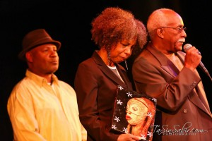 Lifetime Achievement Award winners Emory Douglas and Karen Johnson stand in support as Gregory Johnson speaks of the courage and persistent resistance that will prevail in the epic struggle to reclaim the historic landmark home of Marcus Book Store, heisted by the notorious Sweiss family, enraging the entire Black community. – Photo: TaSin Sabir