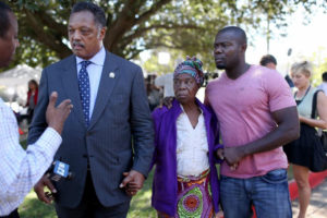 Rev. Jesse Jackson speaks to the media with Nowai Korkoyah, the mother of Ebola victim Thomas Eric Duncan, and his nephew, Joe Weeks, at Texas Health Presbyterian Hospital on Oct. 7, the day before Duncan's death. – Photo: Joe Raedle, NY Daily News