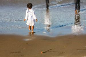 A little girl wades into the ocean following older folk despite the giant waves at Maafa 2014. – Photo: TaSin Sabir