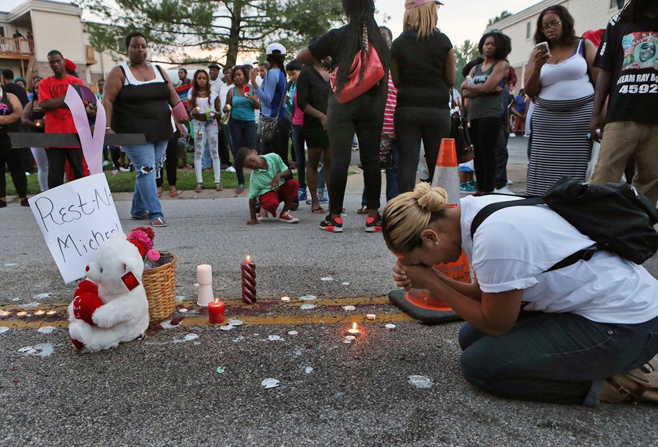 """Cheris Place writes: """"Immediately after the shooting, people poured out in the streets in shock and sympathy for the family. It started out as a peaceful protest and a candlelight memorial for this young man. However, Ferguson and St. Louis County sent in cops in riot gear, and reportedly allowed their dog to urinate on the flowers Michael's mother had put over his blood."""""""