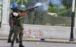 """U.N. troops firing tear gas at Haitian protesters stand in front of a wall with graffiti saying """"Titid,"""" Haitians' affectionate name for the forcibly removed elected Haitian President Jean-Bertrand Aristide. – Photo: United Nations Photo"""