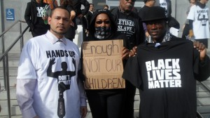 """Vanessa Banks stands with San Francisco Deputy Public Defender Kevin Mitchell (left) and Cephus """"Uncle Bobby"""" Johnson at a Dec. 18 rally outside San Francisco City Hall."""