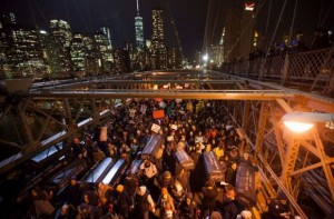 Shutting down major thoroughfares throughout New York City following the nonindictment of Eric Garner's murderer, protesters carry mock coffins across the Brooklyn Bridge bearing the names of people who have been killed in police encounters. – Photo: Michael Nagle, European Pressphoto Agency