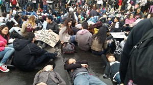 The 200 high schoolers and, in the foreground, some younger students from Deecolonize Academy staged a die-in on the rain-soaked pavement outside Fruitvale BART. – Photo: Poor News Network