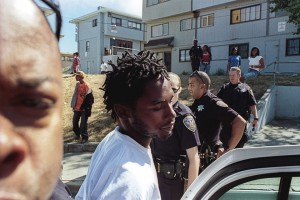 """A young man, Jermaine Jackson, is arrested at Hunters View, one of San Francisco's largest public housing projects, in this 2009 photo. Hunters View is the scene of the city's most dramatic privatization scheme, and in 2009 hundreds of families were fighting eviction, most unsuccessfully. """"With the amount of families in Hunters View dwindling by the month,"""" the photographer observes, """"tension between police and the remaining residents runs high."""" Occupying police targeted Black youth, who were feared as potential resistance leaders. In this arrest, police claimed they had seen Jackson driving recklessly earlier that day. – Photo: Alex Welsh"""