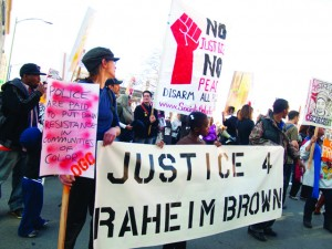 Countless marches, rallies and protests sought justice for Raheim Brown. Here, supporters carried his banner at the annual Oscar Grant Memorial March and Rally on Jan. 1, 2012. – Photo: Bradley Stuart, Indybay