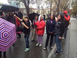"Students from Deecolonize Academy, sponsored by POOR Magazine at Homefulness in Deep East Oakland, chant, ""We're not afraid of the OPD,"" at #ShutdownOPD on the rain-soaked morning of Dec. 15. – Photo: BGD"