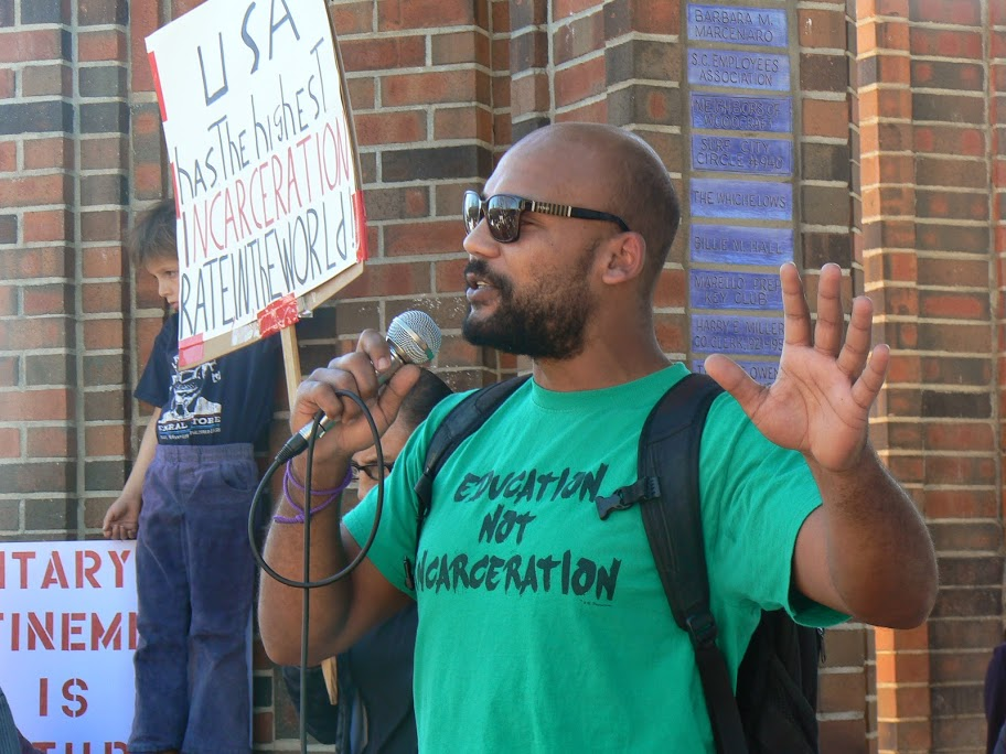 At the Clock Tower rally that kicked off the event, Dru Glover of Project: Pollinate said that lack of access to jobs, healthcare, education and positive, constructive activities make people of color prime targets for police brutality, as they attempt to survive and/or to self-medicate to deal with the stress. He said one in four Black men go to prison in their lifetime. – Photo: Lori Nairne